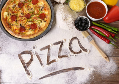The word Pizza written in flour with various ingredients.
